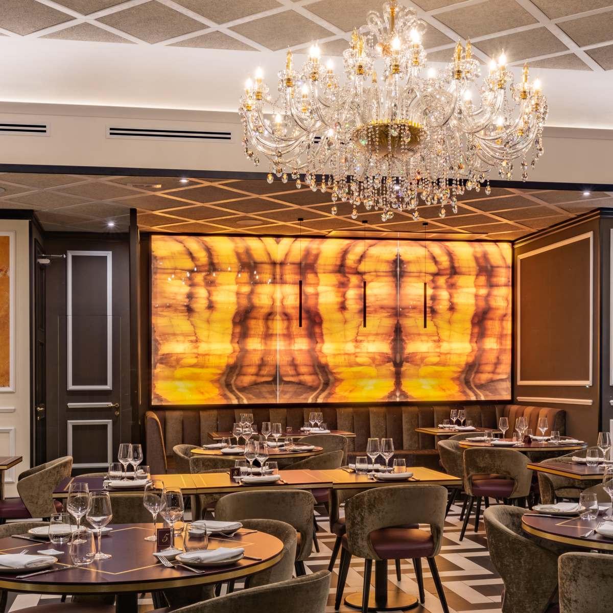 sala interna ristorante con tavoli in legno e sedie in velluto e lampadario di cristallo