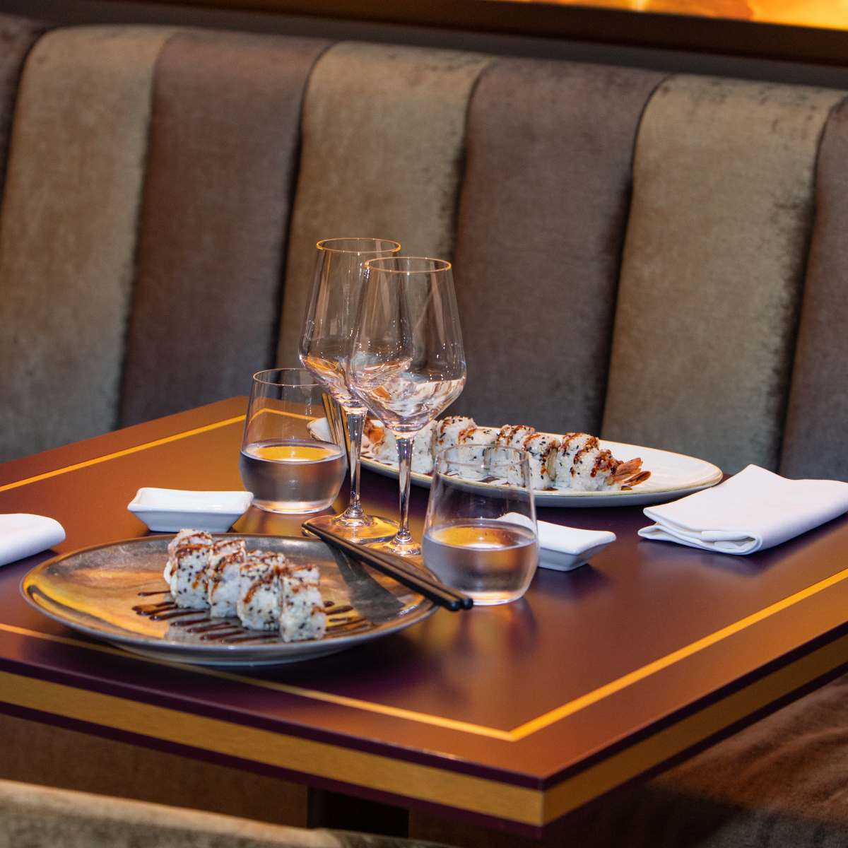 tavolo di legno quadrato apparecchiato per 2 con sushi rool e bacchette