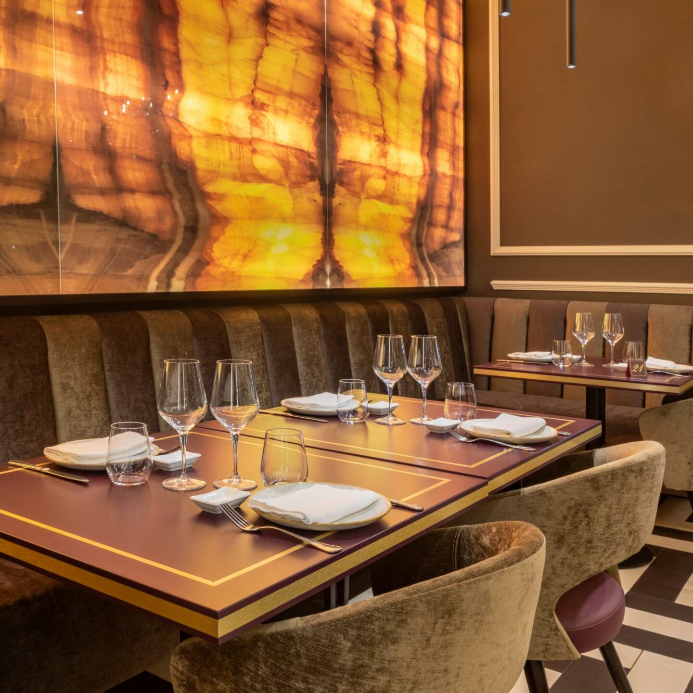 3 tavoli in legno apparecchiati senza tovaglia, con piatti, bicchieri, calici, porta soia e poltrone in velluto. Pavimento bianco e nero e parete luminosa in legno.