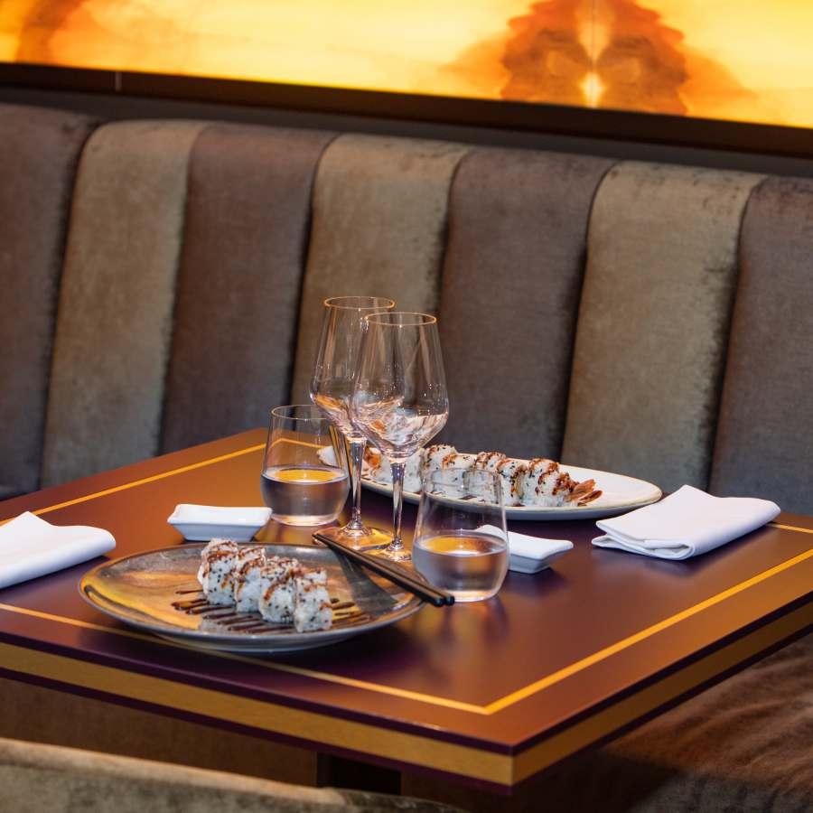 tavolo di legno senza tovaglia con 2 piatti bianchi con sushi roll, 2 calici e 2 bicchieri d'acqua