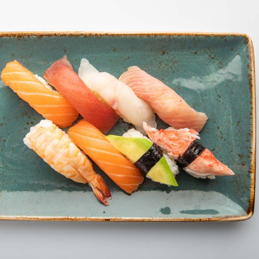 8 nigiri misti su piatti di ceramica verde acqua