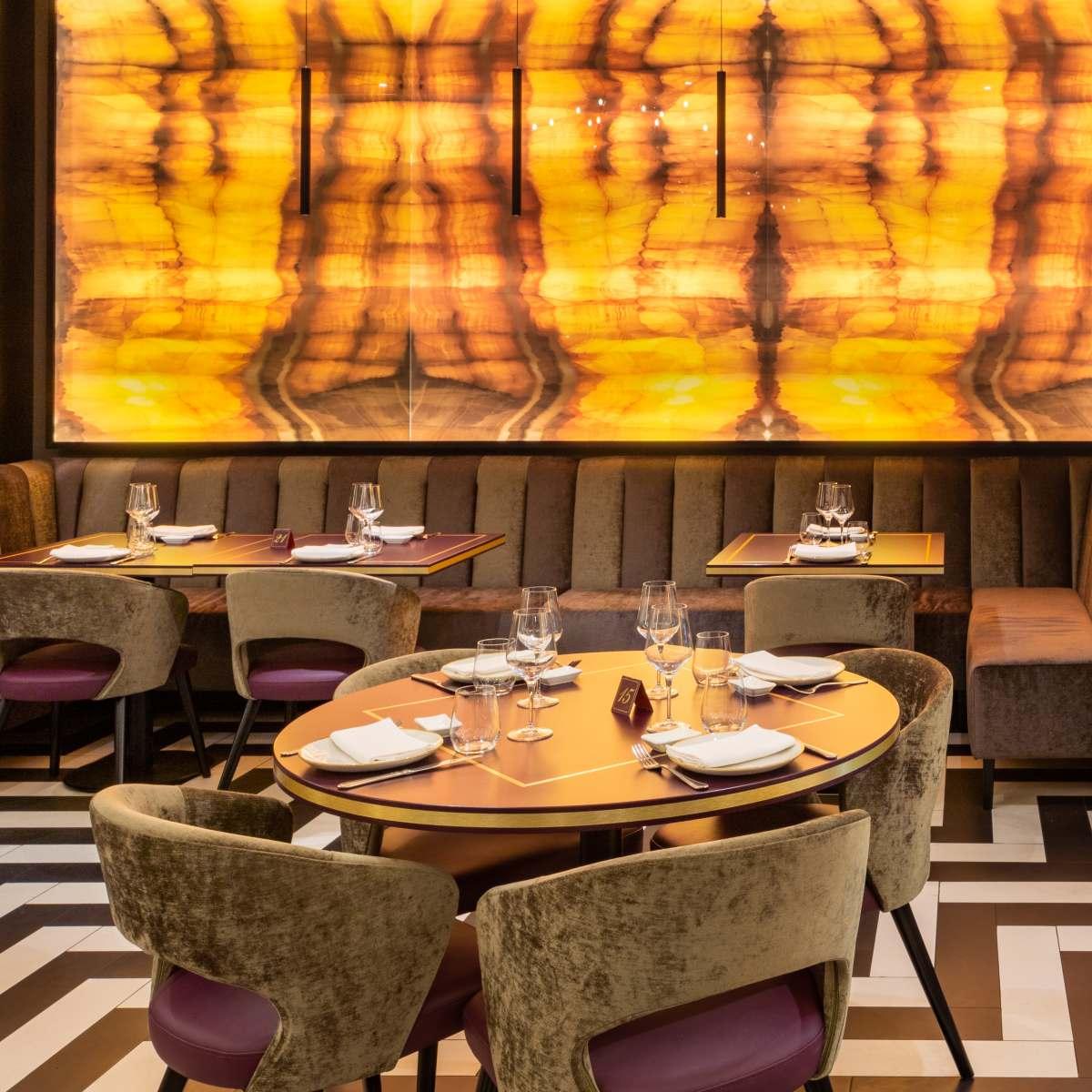 interno ristorante con tavoli in legno, poltrone in velluto, pareti in legno luminose