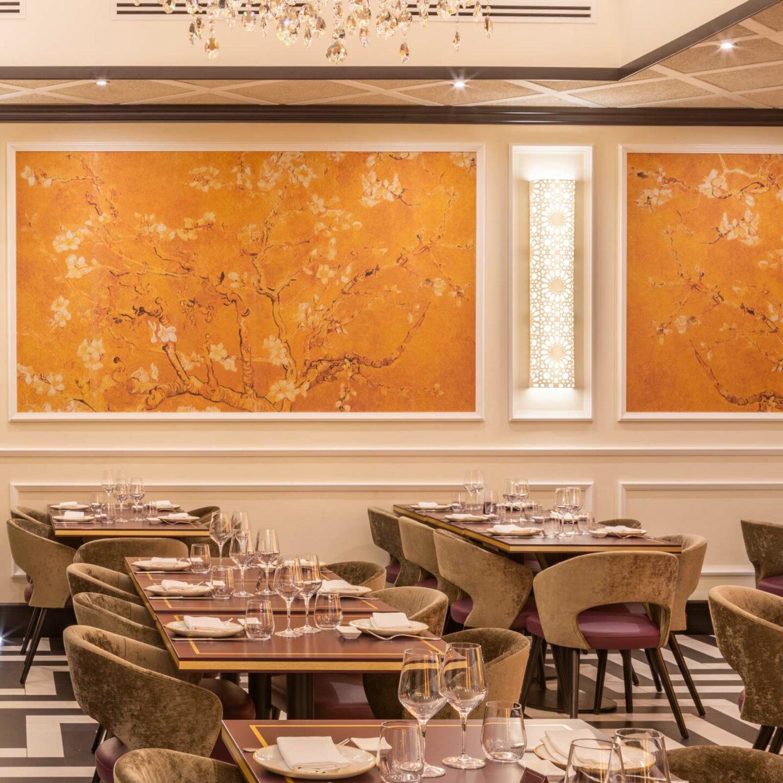 sala ristorante interna con tavoli in legno, pavimento bianco e nero, bicchieri e calici