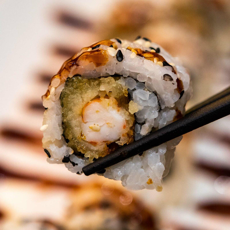 dettaglio sushi roll con bacchette nere
