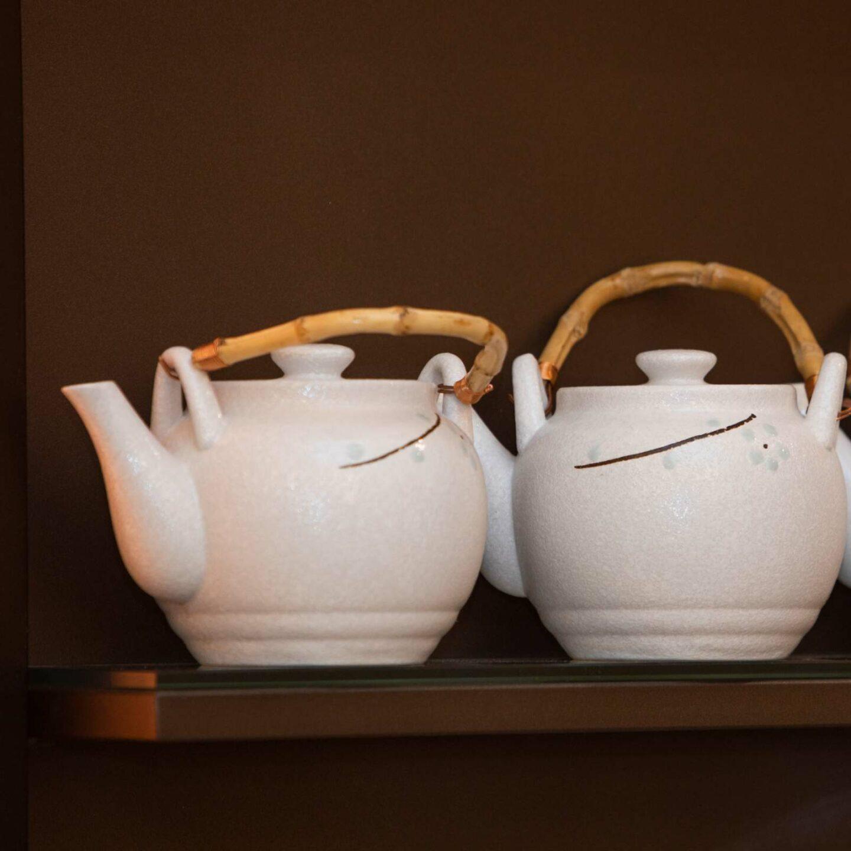 2 teiere bianche con manico in bambu su mensola